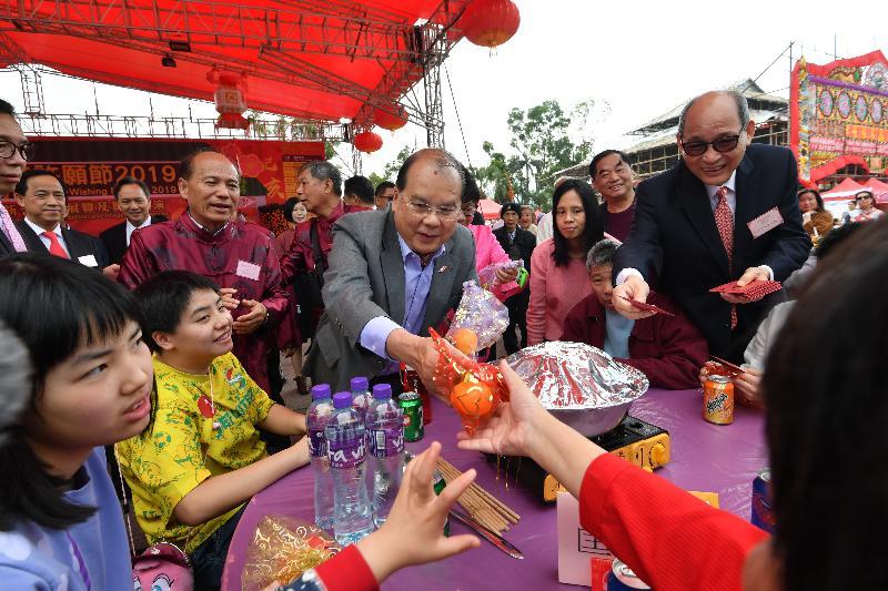 政務司司長張建宗今日(二月五日)出席在大埔林村舉行的香港許願節2019。圖示張建宗(左四)向在場人士派發新年禮物。
