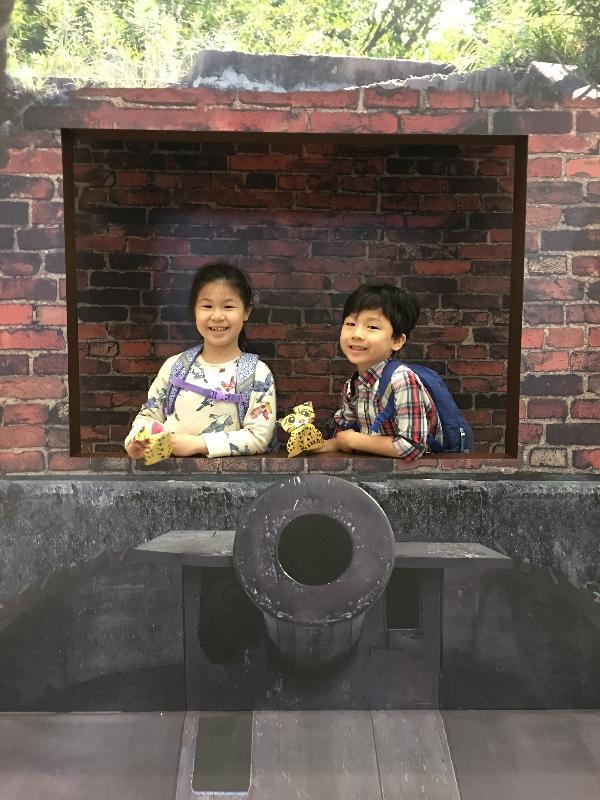 政 府 於 二 月 十 六 日 就 「 提 升 香 港 郊 野 公 園 及 特 別 地 區 康 樂 及 教 育 潛 力 」 的 建 議 方 案 展 開 公 眾 諮 詢 , 以 收 集 公 眾 意 見 。 政 府 建 議 為 這 些 位 於 郊 野 公 園 及 特 別 地 區 內 的 文 化 遺 產 設 立 開 放 式 博 物 館 , 並 舉 辦 不 同 的 教 育 活 動 , 讓 市 民 了 解 香 港 歷 史 。 圖 示 小 朋 友 於 展 覽 內 的 展 品 拍 照 留 念 。