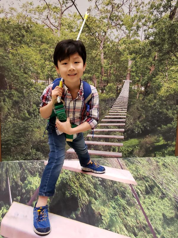 政 府 於 二 月 十 六 日 就 「 提 升 香 港 郊 野 公 園 及 特 別 地 區 康 樂 及 教 育 潛 力 」 的 建 議 方 案 展 開 公 眾 諮 詢 , 以 收 集 公 眾 意 見 。 圖 示 小 朋 友 在 展 覽 內 以 樹 頂 歷 奇 為 主 題 的 3D拍 照 區 留 影 。