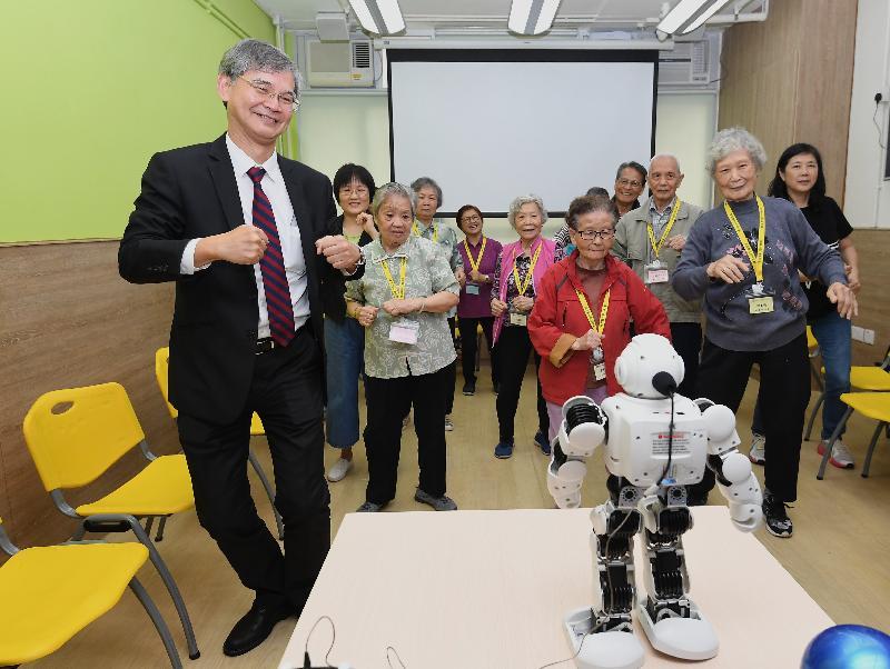 勞工及福利局局長羅致光博士(左一)今日(三月二十二日)到訪香港耆康老人福利會柴灣長者地區中心,了解樂齡科技的應用。