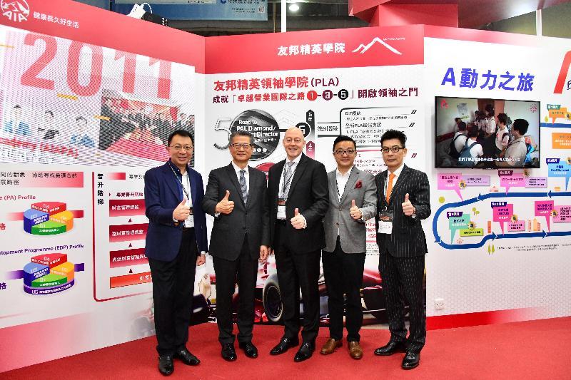 財政司司長陳茂波今日(三月二十三日)出席友邦精英學院:創新香港國際人才嘉年華2019開幕儀式。圖示陳茂波(左二)在開幕儀式前參觀展覽攤位並與嘉賓合照。