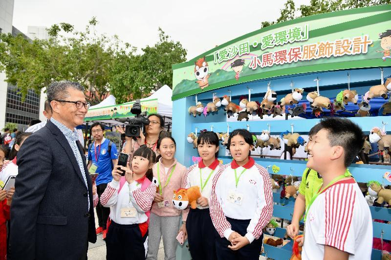財政司司長陳茂波今日(三月三十日)出席2018沙田節閉幕禮「愛沙田」親子遊藝節。圖示陳茂波(左一)參觀攤位,並與學生記者交談。