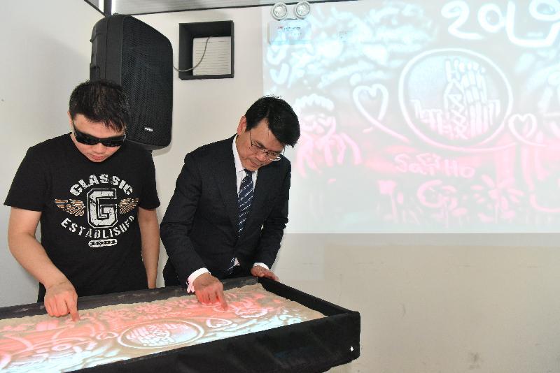 商務及經濟發展局局長邱騰華(右)今日(四月十二日)到訪觀塘區,並到毗鄰觀塘海濱的「反轉天橋底二三號場」參觀一個藝術工作坊,其間與職員一起製作沙畫。
