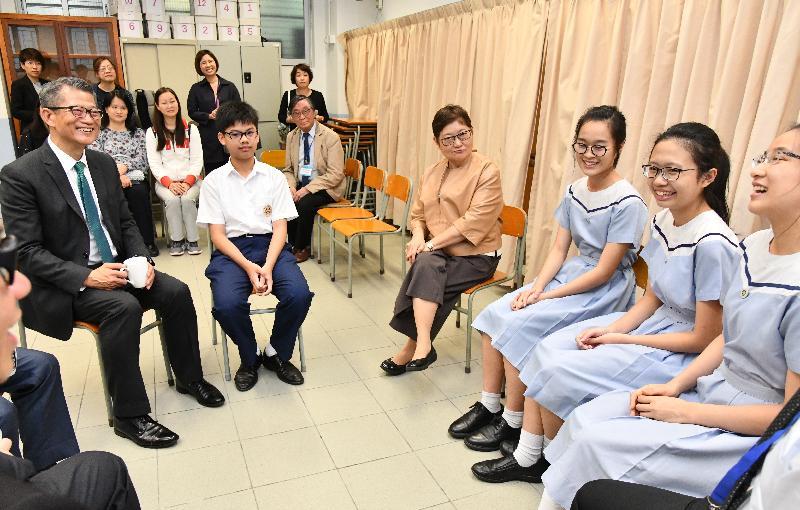 財政司司長陳茂波今日(五月七日)到訪葵青區的聖公會林護紀念中學。圖示陳茂波(左一)在校監郁德芬博士(右四)陪同下與學生交流。