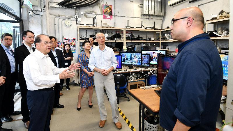 政務司司長張建宗(前排左)今日(五月十五日)在環境局局長黃錦星(前排中)陪同下參觀WEEE.PARK內的復修工場,了解如何把一些仍可運作的舊電器修復成「再生電器」。