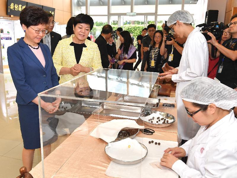 行政長官林鄭月娥今日(五月二十四日)上午出席北京同仁堂2019年首都國企開放日。圖示林鄭月娥(左一)參觀示範,了解中藥製品製作過程。