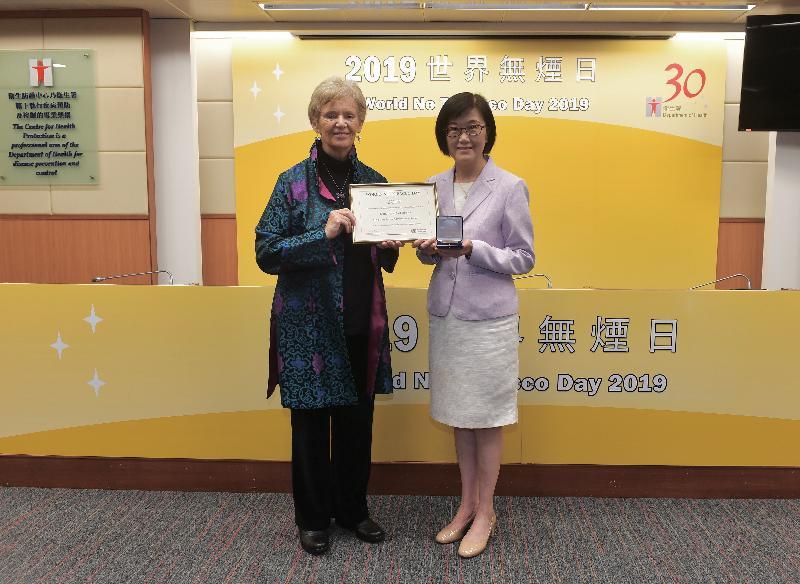 衞生署署長陳漢儀醫生(右)今日(五月三十日)代表衞生署,接受世界衞生組織資深政策顧問麥龍詩迪教授(左)頒發的「世界無煙日獎」,肯定香港在控煙工作方面的努力。