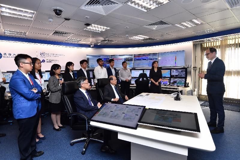 政務司司長張建宗今日(七月十五日)到訪香港天文台。圖示張建宗(前排右)在天文台台長岑智明(前排左)陪同下,聽取天文台署理助理台長(輻射監測及評估)馬偉民(右一)介紹天文台輻射監測工作上的最新情況。