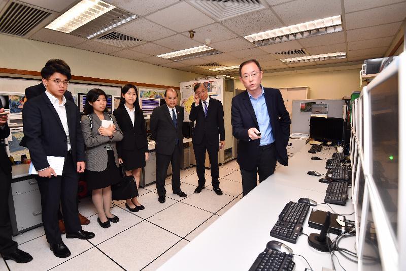 政務司司長張建宗今日(七月十五日)到訪香港天文台地震監測及海嘯警報中心。圖示張建宗(右三)在天文台台長岑智明(右二)陪同下,聽取中心人員介紹天文台從香港及世界各地的地震站收集及分析實時的地震數據,以及向公眾發放有關地震消息的程序。