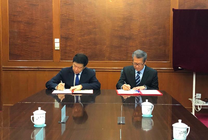 財政司司長陳茂波(右)今日(七月十九日)在北京與國家稅務總局局長王軍(左)簽訂《內地和香港特別行政區關於對所得避免雙重徵稅和防止偷漏稅的安排》第五議定書。