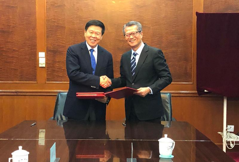 財政司司長陳茂波(右)今日(七月十九日)在北京與國家稅務總局局長王軍(左)簽訂《內地和香港特別行政區關於對所得避免雙重徵稅和防止偷漏稅的安排》第五議定書後握手。