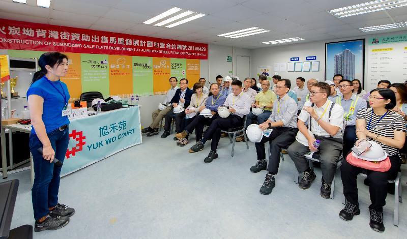 香港房屋委員會轄下建築小組委員會多名委員今日(七月二十五日)參觀沙田旭禾苑的工地。圖示小組委員聆聽房屋署代表簡報在各種限制下的地盤安全措施