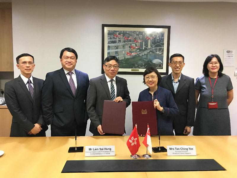 The Permanent Secretary for Development (Works), Mr Lam Sai-hung, and the Permanent Secretary of the Ministry of Finance of Singapore, Mrs Tan Ching-yee, sign a Memorandum of Understanding in Singapore today (July 30) to enhance collaboration in exchanging expertise and experience in infrastructure project management and delivery. Photo shows Mr Lam (third left); Mrs Tan (third right); representative of the Project Strategy and Governance Office of the Development Bureau, Mr John Kwong (second left); and the Executive Director of the Centre for Public Project Management of the Ministry of Finance of Singapore, Mr Chia Ser-huei (second right), at the signing ceremony.