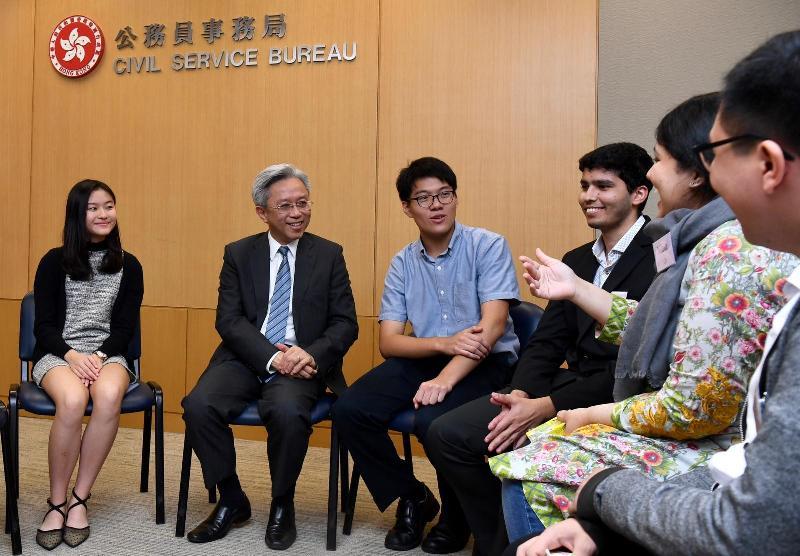公務員事務局局長羅智光今日(七月三十一日)在政府總部與參加非華裔大學生政府部門實習計劃的學生茶敍。圖示羅智光(左二)與實習同學交談,了解他們的實習體驗。兩名參與「與香港同行」計劃的中學生(左一及左三)亦有參與茶敍。