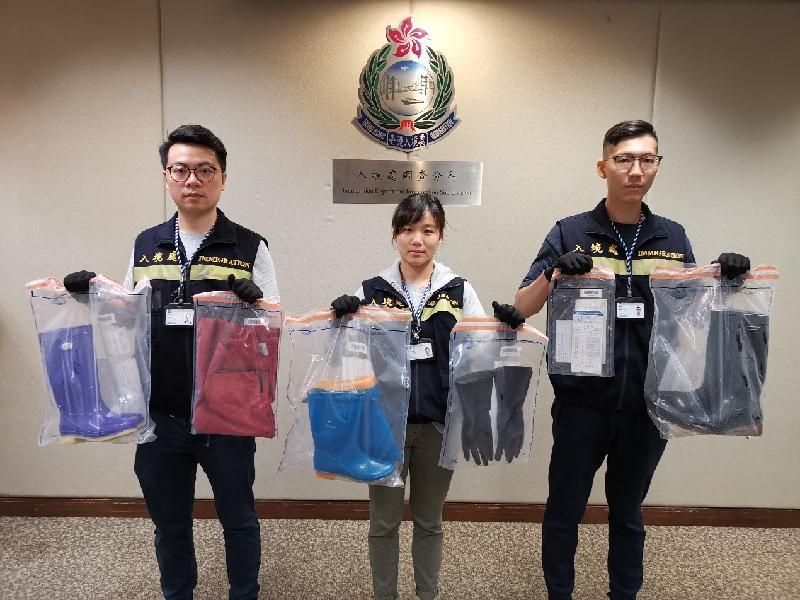入境事務處昨日(八月十二日)在香港區展開代號「曙光行動」的反非法勞工行動。圖示入境處人員展示行動中檢取的證物。