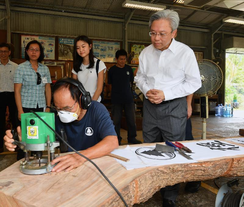 公務員事務局局長羅智光今日(八月十四日)到訪漁農自然護理署元朗大棠苗圃。圖示羅智光(右一)在大棠工場觀看專責同事為郊野公園製作木材設施的情況。