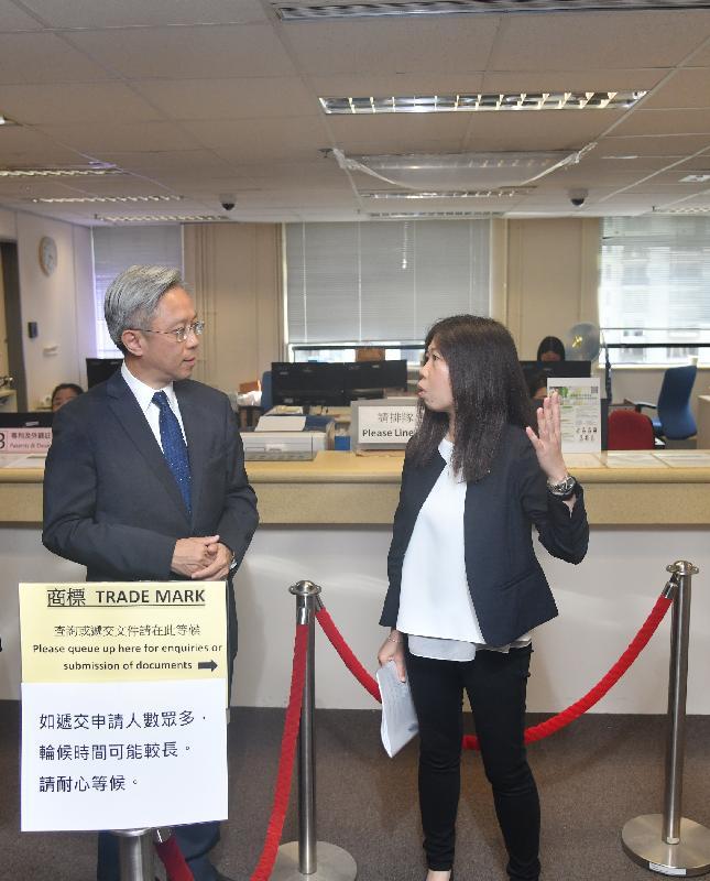 公務員事務局局長羅智光今日(九月十三日)到訪知識產權署。圖示羅智光(左)聽取同事介紹公眾服務櫃檯提供的服務。
