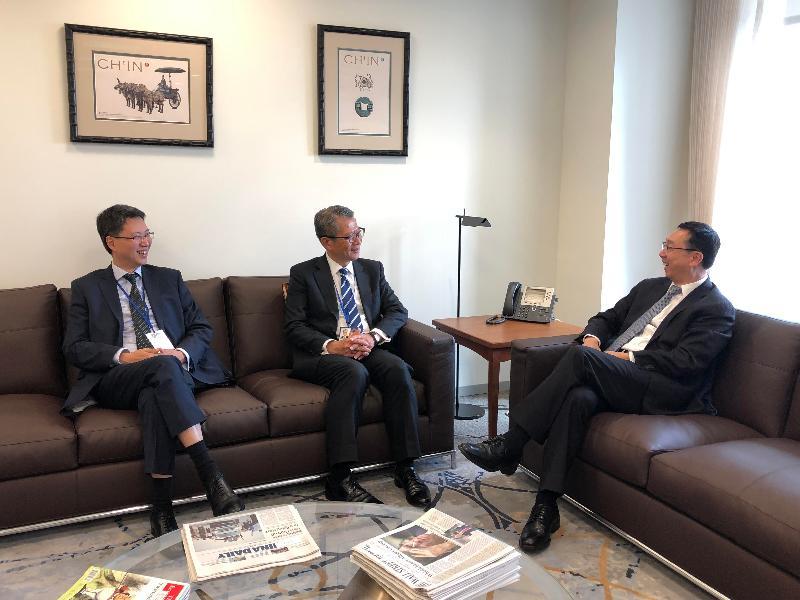 財政司司長陳茂波(中)和香港駐美國總經濟貿易專員麥德偉(左)昨日(美國東岸時間十月十七日)在美國華盛頓與國際貨幣基金組織副總裁張濤(右)會晤。