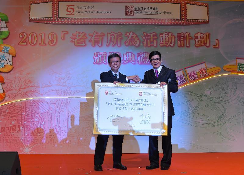 社會福利署署長梁松泰(左)今日(十一月一日)在2019「老有所為活動計劃」頒獎典禮頒發委任狀予「老有所為活動計劃」榮譽宣傳大使安德尊(右)。