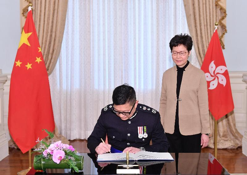 新任警務處處長鄧炳強(左)今日(十一月十九日)在宣誓後簽署誓言。