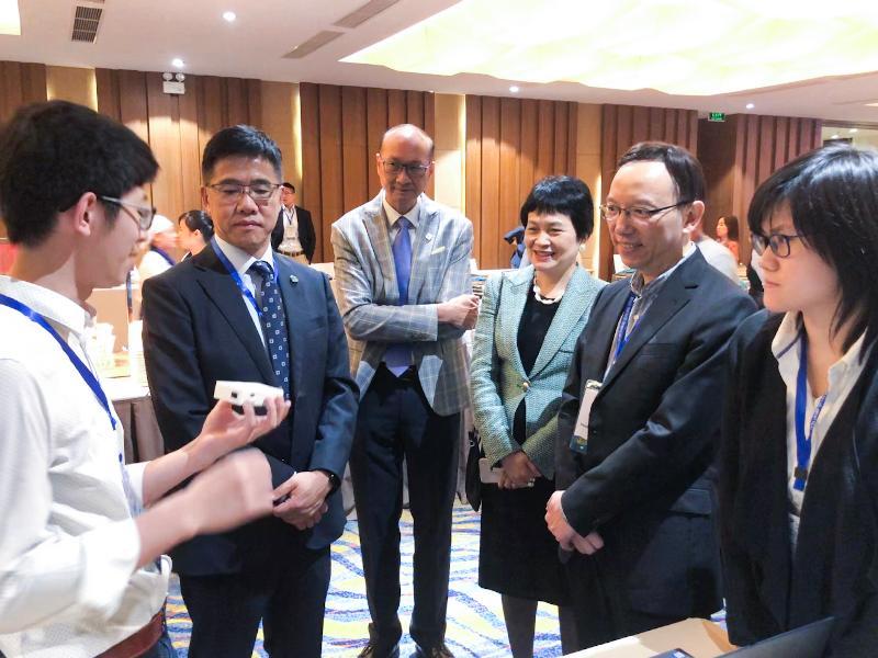 政府資訊科技總監林偉喬(右二)十一月二十一日在越南下龍舉行的第十九屆亞太資訊及通訊科技大獎「香港之夜」活動上聽取香港代表介紹其創新作品。