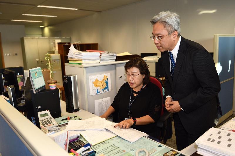 公務員事務局局長羅智光今日(十一月二十七日)到訪工業貿易署。圖示羅智光(右)在制度部聽取同事介紹處理《內地與香港關於建立更緊密經貿關係的安排》原產地證書申請的工作。