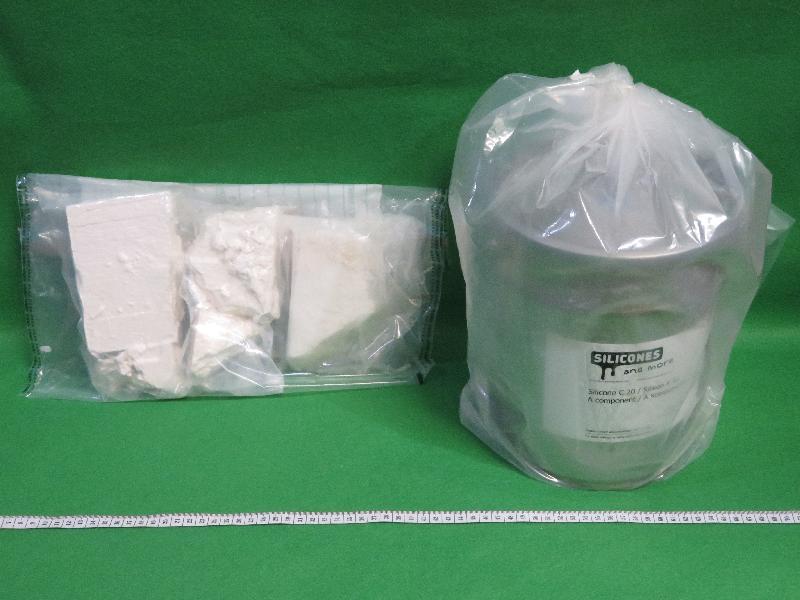 香港海關十一月二十二日及二十三日在香港國際機場分別檢獲約五百二十克懷疑氯胺酮及約一公斤懷疑可卡因,估計市值共約一百六十萬元。圖示檢獲的懷疑可卡因及用作收藏毒品的金屬容器。