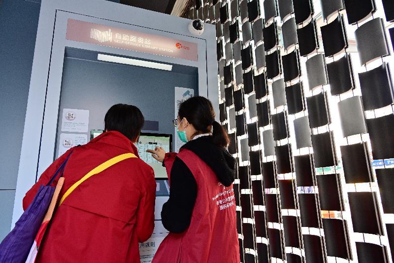 康樂及文化事務署香港公共圖書館今日(一月十五日)在大圍推出全港第三個自助圖書站,加強為市民提供二十四小時的公共圖書館服務。圖示服務大使協助市民使用圖書站。