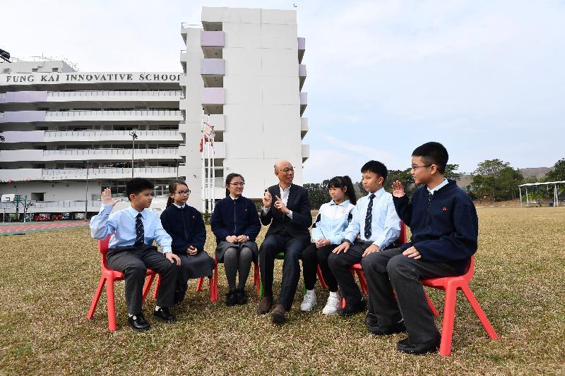 環境局局長黃錦星(中)昨日(一月二十日)到訪上水鳳溪創新小學,與學生分享減緩氣候變化的個人及校園經驗。