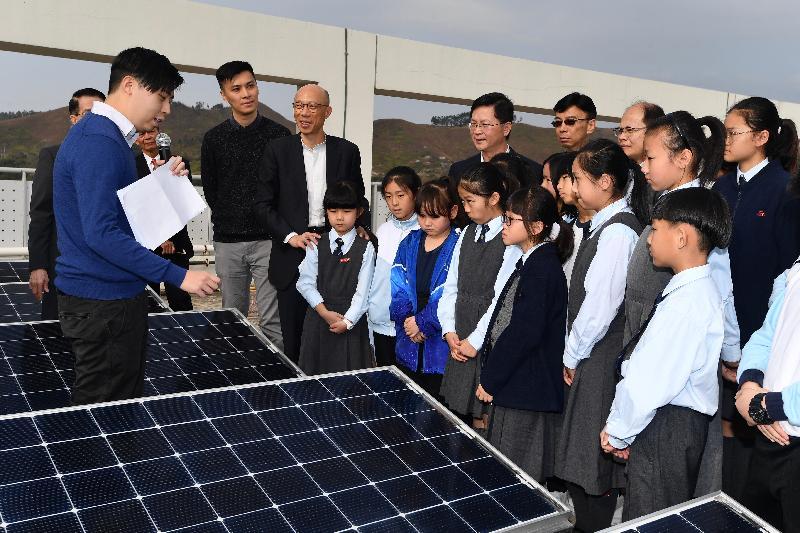 環境局局長黃錦星(左三)昨日(一月二十日)到訪上水鳳溪創新小學,視察位於學校天台的太陽能板,並聽取有關太陽能發電系統的環保元素及設計概念的簡介。