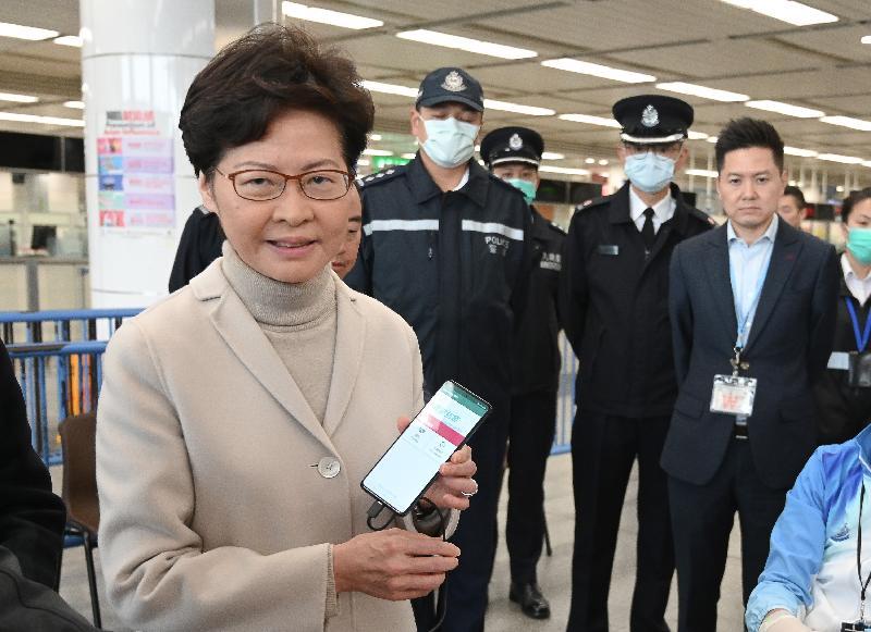 林鄭月娥(左一)在深圳灣口岸了解如何為須檢疫人士佩戴電子手環,以監察他們有否留在居所。圖示林鄭月娥與配合電子手環使用的手機。