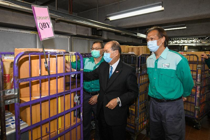 政務司司長張建宗(中)今日(二月十七日)到訪香港郵政,視察處理內載口罩的特快專遞郵件流程。