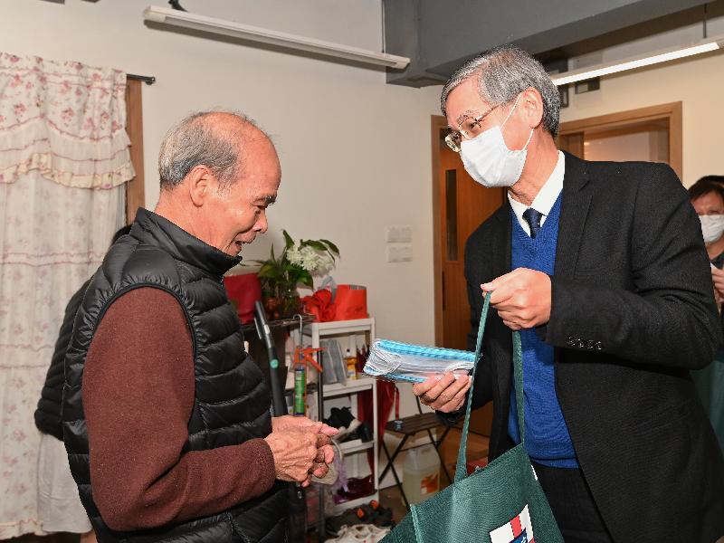 勞工及福利局局長羅致光博士(右)今日(二月十七日)傍晚到大角咀,向長者派發口罩及防疫福袋。