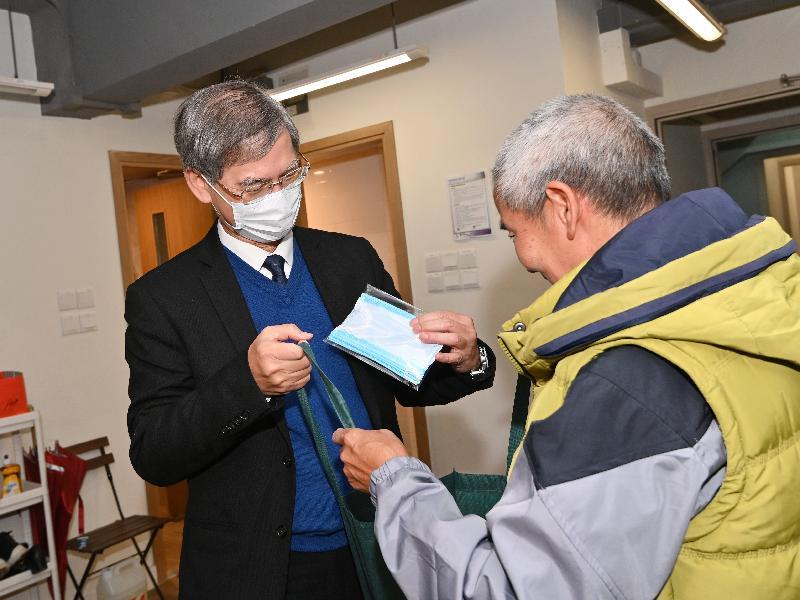 勞工及福利局局長羅致光博士(左)今日(二月十七日)傍晚到大角咀,向長者派發口罩及防疫福袋。
