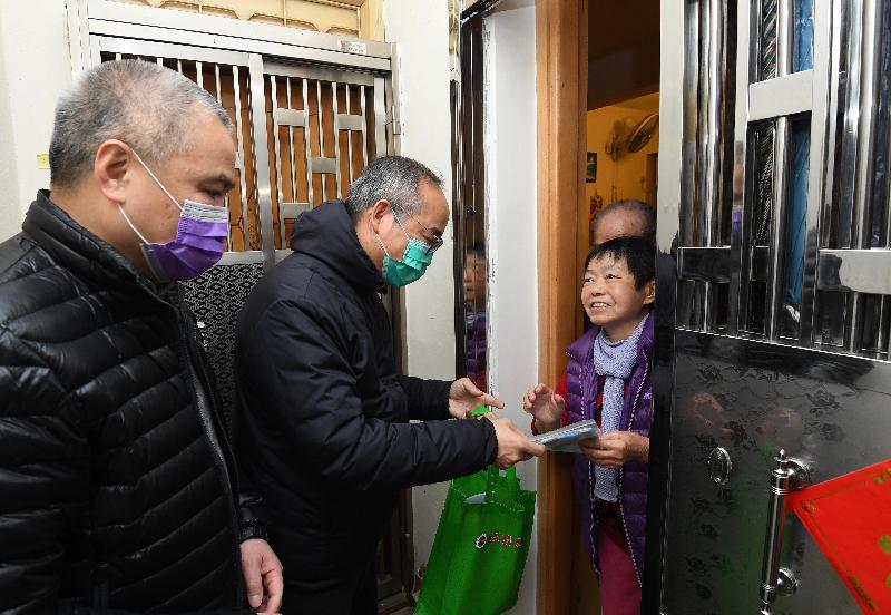 民政事務局局長劉江華(中)今日(二月十七日)到訪居於旺角的市民,為他們送上包括口罩的抗疫用品。