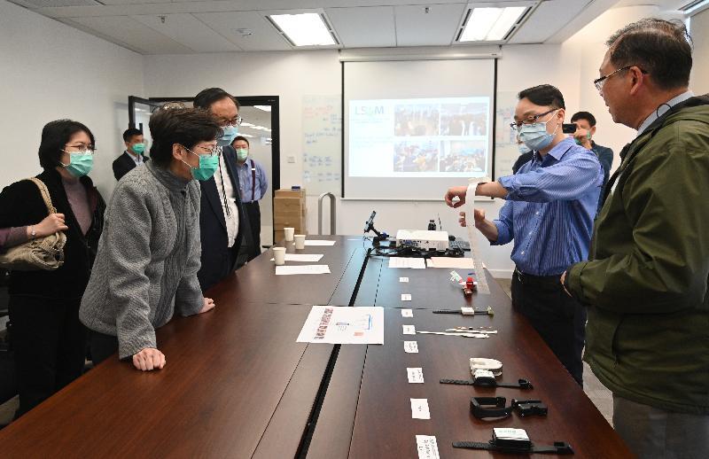 行政長官林鄭月娥今日(二月二十日)下午探訪香港科學園內的物流及供應鏈多元技術研發中心,聽取負責人介紹該公司為政府研發和生產用於家居檢疫的電子手環的工作。圖示林鄭月娥(左三)在創新及科技局局長楊偉雄(左四)陪同下,聽取負責人分享研發和生產手環過程。