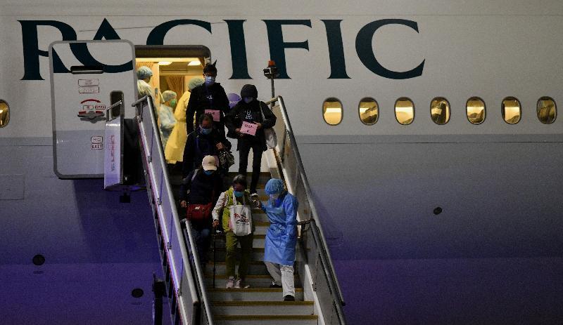 由香港特別行政區政府安排接載「鑽石公主號」郵輪上的香港居民的第二班包機今日(二月二十二日)凌晨抵達香港。圖示一名工作人員陪同香港居民離開包機。