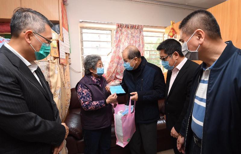政務司司長張建宗(中)今日(二月二十二日)在東區民政事務專員陳尚文(左一)陪同下到訪北角健康村,向長者派發口罩等抗疫物資。