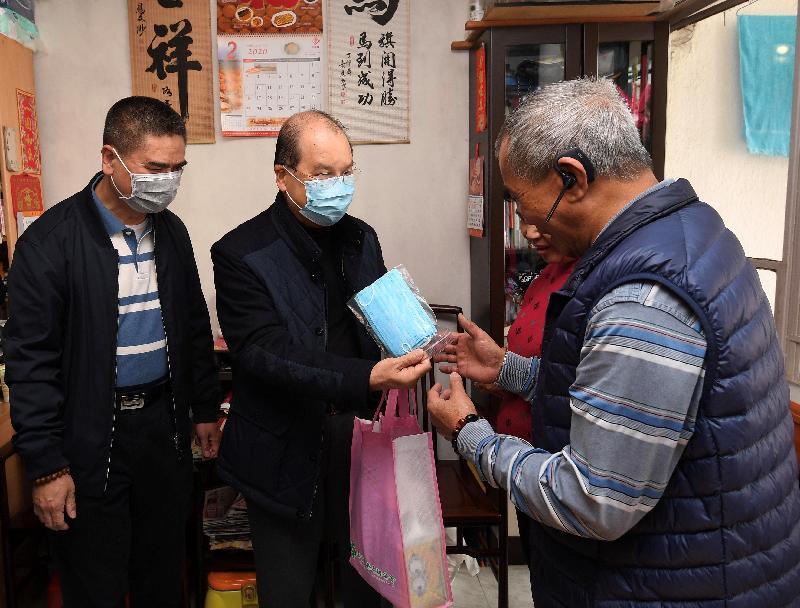 政務司司長張建宗(左二)今日(二月二十二日)到訪北角健康村,向住戶派發口罩等抗疫物資。