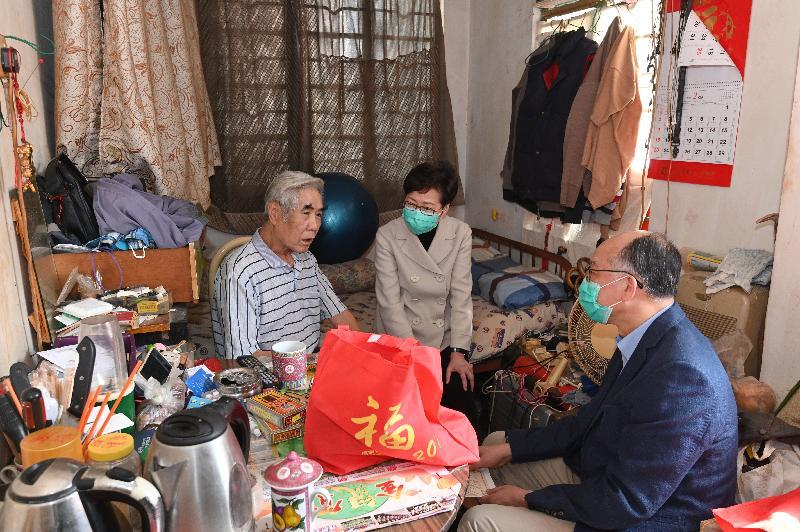 行政長官林鄭月娥(中)和運輸及房屋局局長陳帆(右)今日(二月二十五日)下午到訪深水埗,向居於「劏房」的長者派發口罩等防疫用品。