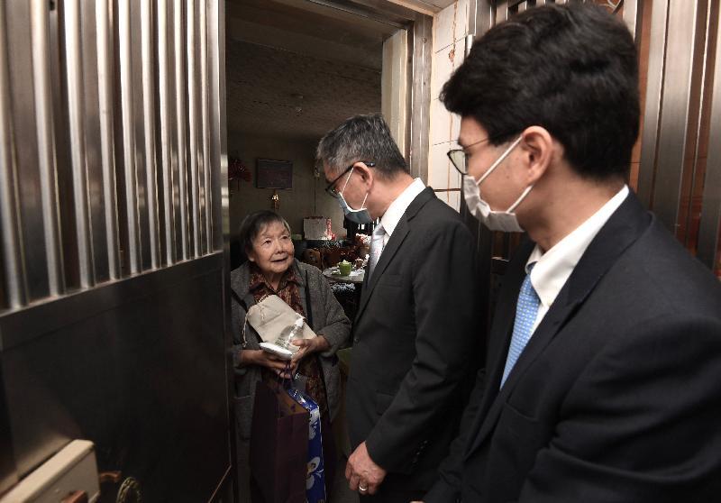 財經事務及庫務局局長劉怡翔(中)和副局長陳浩濂(右)今日(二月二十八日)到中西區探訪長者,向他們派發口罩等防疫物資。