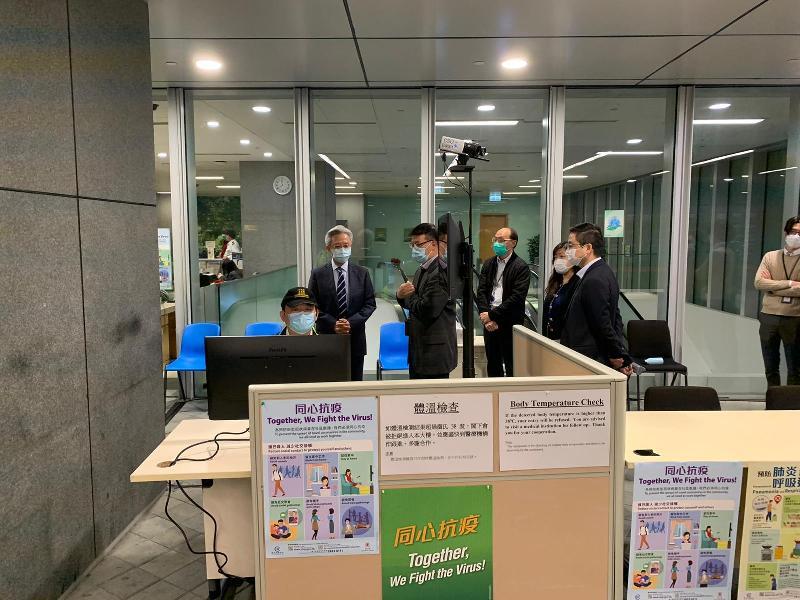 公務員事務局局長羅智光(左二)今日(三月二日)在政府總部聽取同事簡介各項防疫措施。