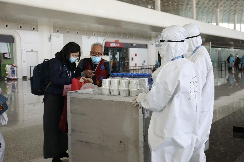 Crew members from the airline company serving refreshment, such as cup noodles and bottled water, to Hong Kong residents stranded in Hubei Province before they board the chartered flight at the Wuhan Tianhe International Airport today (March 4).