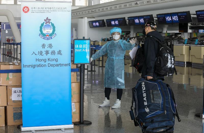 香港特別行政區政府今日(三月四日)安排首批專機,接載滯留在湖北省的香港居民回港,圖示入境事務處人員在武漢天河國際機場為乘坐包機的港人指示離境程序。