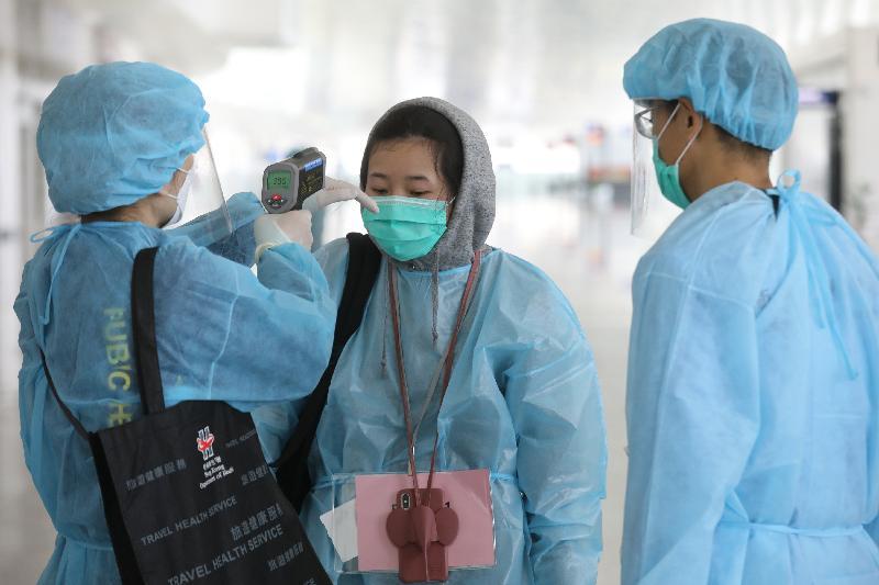 滯留湖北的香港居民今日(三月四日)在武漢天河國際機場登機前,接受衞生署人員量度體溫。