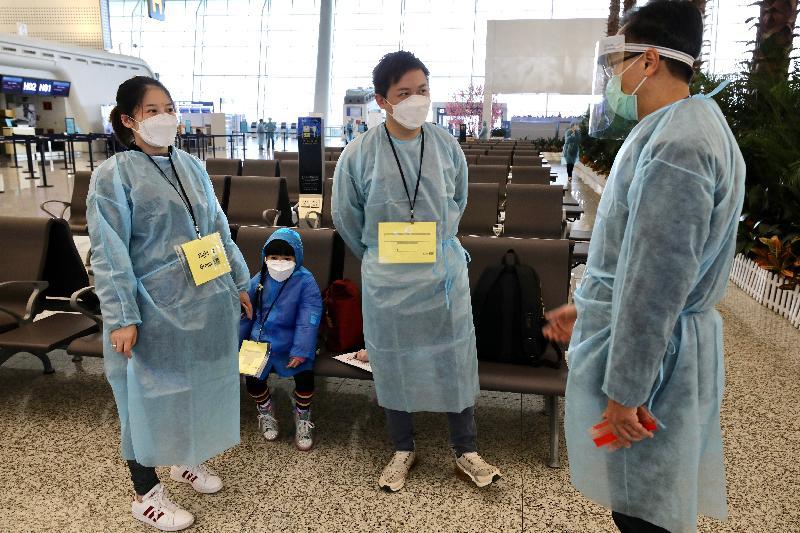 政制及內地事務局局長聶德權(右一)今日(三月四日)在武漢天河國際機場,向正在等候上機的一個滯留湖北省的香港家庭,包括一名孕婦致以問候。