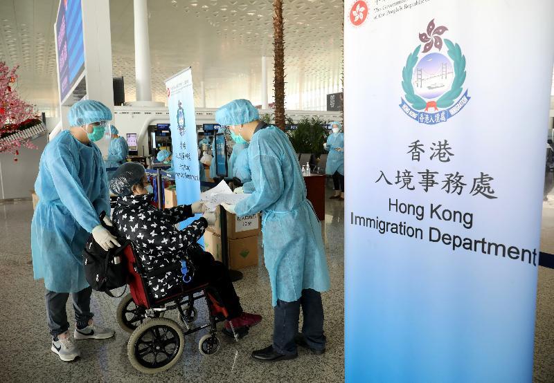 入境事務處(入境處)人員今日(三月五日)在武漢天河國際機場,協助滯留在湖北省的港人登上專機返港。圖示入境處人員為一名需輪椅輔助的人士登記資料。