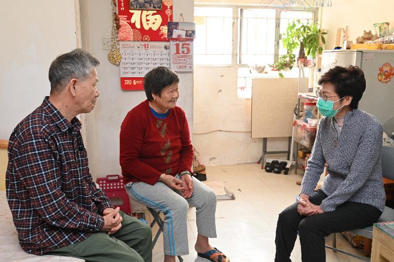 行政長官林鄭月娥今日(三月十五日)到天水圍和流浮山,參與香港義工聯盟派發口罩的活動。圖示林鄭月娥(右一)探訪天水圍天恩邨有長者的家庭,並派發內附口罩的防疫包給他們。