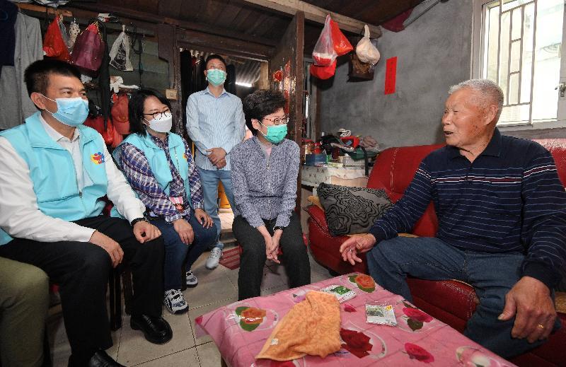 行政長官林鄭月娥今日(三月十五日)到天水圍和流浮山,參與香港義工聯盟派發口罩的活動。圖示林鄭月娥(右二)探訪居住在流浮山鄉村的長者,並派發內附口罩的防疫包給他。