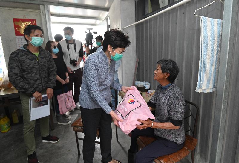 行政長官林鄭月娥今日(三月十五日)到天水圍和流浮山,參與香港義工聯盟派發口罩的活動。圖示林鄭月娥(右二)探訪居住在流浮山鄉村的長者,並派發內附口罩的防疫包給她。